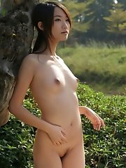 Aspiring nude model from China taking pictures outdoors